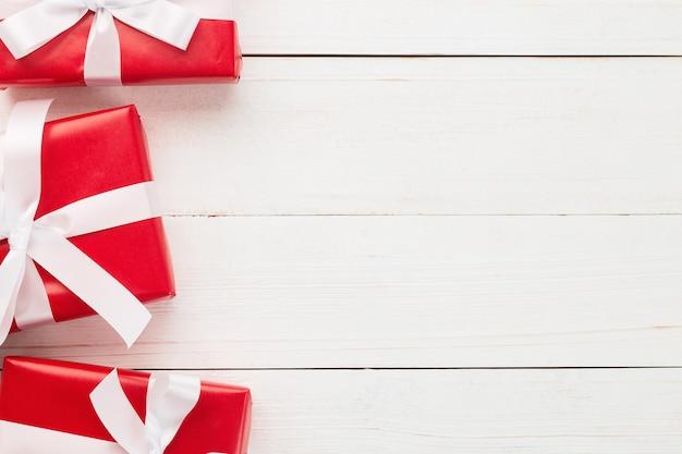 Noël et nouvel an avec décoration de coffrets cadeaux rouges sur fond de table en bois blanc vue de dessus avec espace de copie.