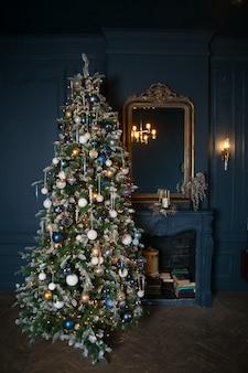 Noël et nouvel an décoré salle intérieure sombre. chambre décorée avec cheminée. soirée de noël festive avec des lumières sur l'arbre avec des cadeaux et des livres.