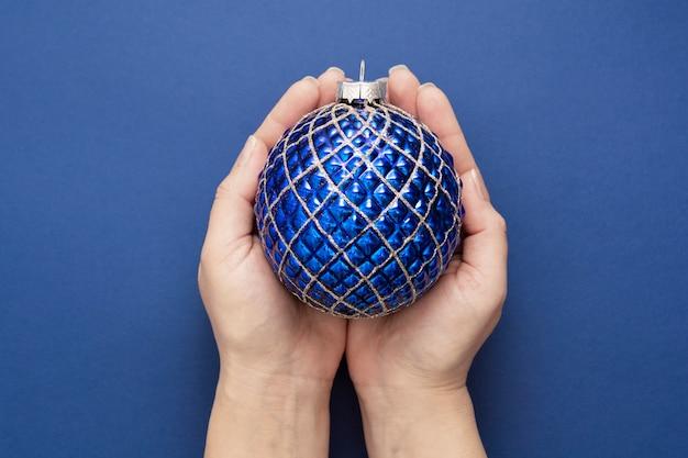 Noël ou nouvel an fond bleu avec des mains féminines tenant une boule décorative d'hiver sur fond bleu, isolé.
