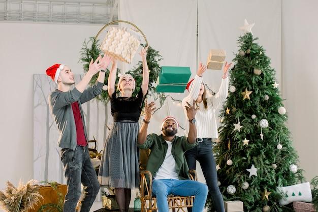 Noël nouvel an vacances d'hiver quatre amis célébrant noël à la maison confortable s'amusant avec des boîtes à cadeaux