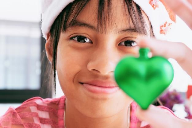 Noël petite fille au chapeau rouge souriant avec des ornements décoratifs et des cadeaux de noël