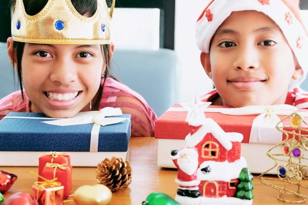 Noël petite fille et garçon portant chapeau rouge souriant avec des ornements décoratifs de noël