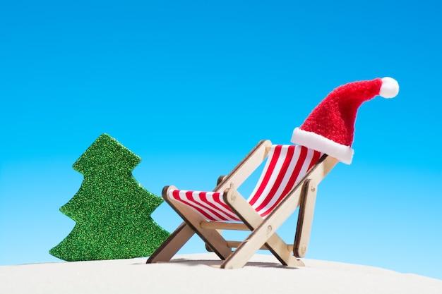 Noël sur la plage: une chaise longue avec bonnet de noel et sapin jouet