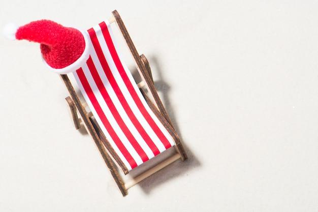 Noël sur la plage: une chaise longue avec un bonnet de noel. vue de dessus