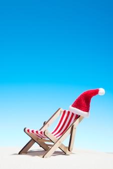 Noël sur la plage: une chaise longue avec un bonnet de noel