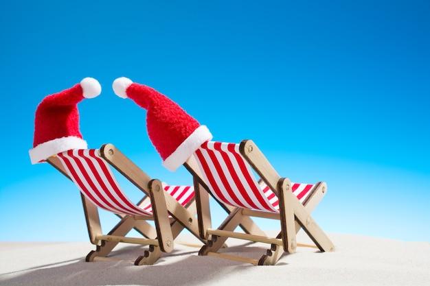 Noël sur la plage: deux chaises et des chapeaux du père noël