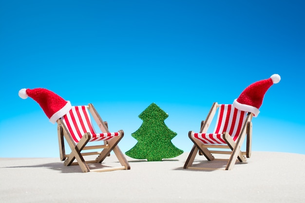 Noël sur la plage: deux chaises avec chapeaux de père noël et sapin jouet