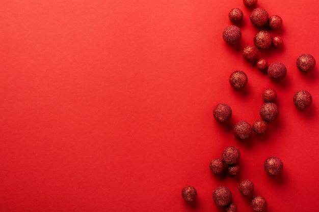 Noël plat poser avec sapin, avec arbre de noël fait de boules de jouets rouges décorées de confettis dorés dans une enveloppe rouge sur rouge.