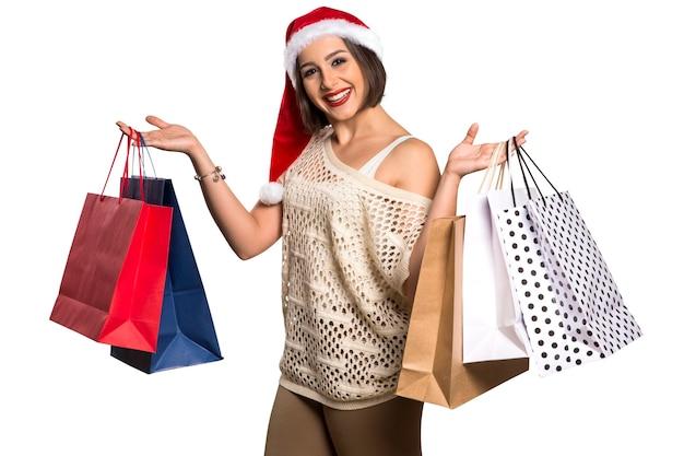 Noël santa hat portrait de femme isolée tenir le cadeau de noël. fille heureuse souriante en fond blanc