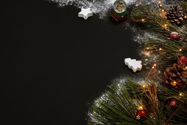 Noël, sapin de noël, décor coloré, étoiles, boules sur fond noir. vue de dessus. espace de copie. nature morte à plat lay nouvel an