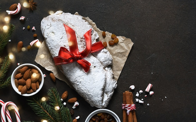 Noël stollen avec ruban rouge en cadeau sur une table en béton.