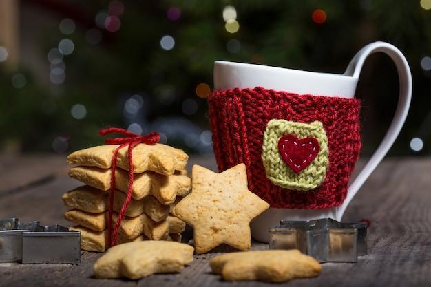 Noël - tasses en laine tricotées et pain d'épice en forme d'étoile sur une table en bois