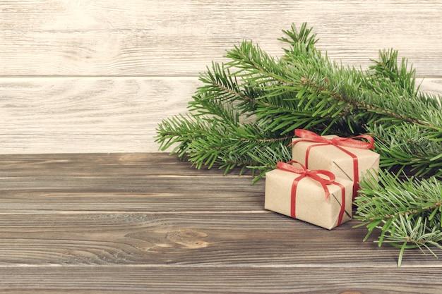 Noël tonique avec cadeau de noël sur fond en bois avec des branches de sapin. composition de noël et bonne année. lay plat, vue de dessus