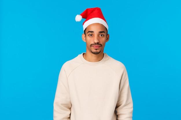 Noël, vacances et concept de famille. un mec afro-américain mignon et idiot célèbre les vacances d'hiver, la maison des parents, portant un chapeau de père noël, se sentant maladroit, assister à la fête du nouvel an, fond bleu