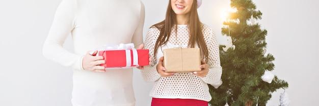 Noël, vacances, saint-valentin et concept d'anniversaire - un homme et une femme heureux tiennent des boîtes avec des cadeaux sur fond blanc avec espace de copie.