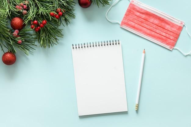Noël vide vide, masque médical de protection rouge sur fond bleu, liste de souhaits de vacances avec espace de copie.