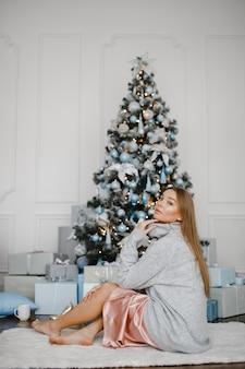 Noël, x-mas, hiver, concept de bonheur - femme souriante avec de nombreux coffrets cadeaux. fille ouvre un cadeau dans le contexte de l'arbre de noël. heureuse jeune femme célébrant noël