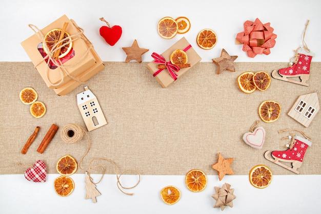 Noël zéro déchet avec des boîtes en carton artisanal, des oranges séchées, une décoration en bois et textile, une mise à plat sans plastique
