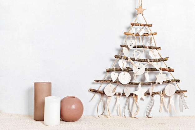 Noël zéro déchet avec des bougies et un arbre de noël fait main alternatif suspendu au mur léger
