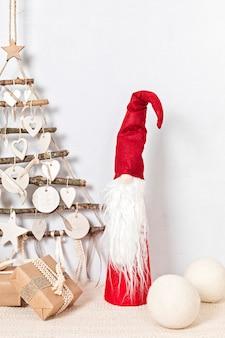 Noël zéro déchet avec des cadeaux emballés dans du papier kraft et un arbre de noël fait main alternatif suspendu au mur léger
