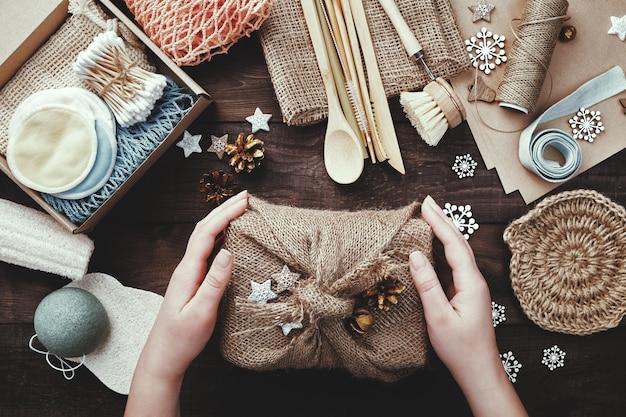 Noël zéro déchet. les mains féminines tiennent le cadeau enveloppé dans de la toile de jute.
