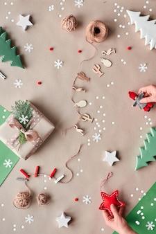 Noël zéro déchet, pose à plat sur fond de papier kraft - guirlande de poupée textile, boîte-cadeau enveloppée, mains féminines tiennent une étoile textile rouge et une poupée.