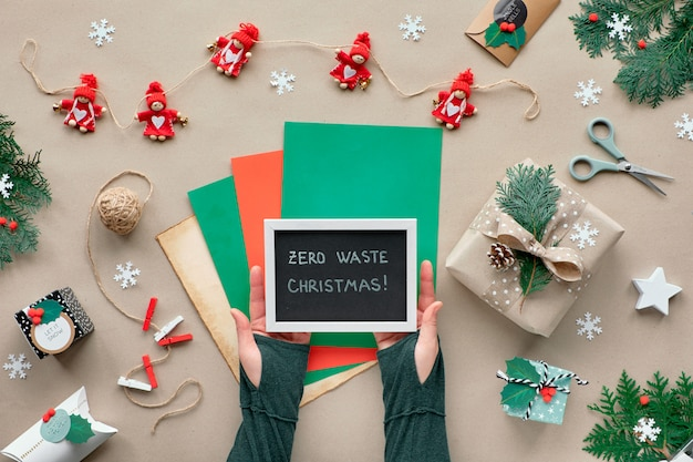 Noël zéro déchet, posé à plat sur un mur de papier kraft avec une guirlande de poupée en textile, des cadeaux emballés, un tableau noir avec le texte