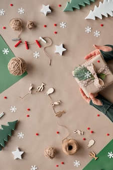 Noël zéro déchet, pose à plat, vue de dessus sur papier kraft - guirlande de poupée textile, cadeaux emballés, mains décorent une boîte-cadeau à la main avec ruban et brindille alternative verte écologique noël.