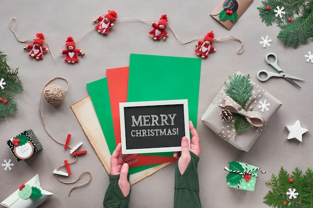 Noël zéro déchet, pose à plat, vue de dessus sur papier kraft avec guirlande de poupée textile, cadeaux emballés, tableau noir avec texte