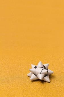 Noeud cadeau brillant sur fond doré pailleté avec espace copie.
