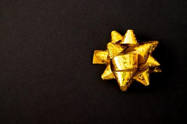 Noeud de cadeau de couleur dorée sur fond noir. noël et nouvel an. un cadeau d'anniversaire. espace vide pour le texte.