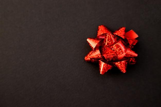 Noeud de cadeau en rouge sur fond noir. noël et nouvel an. un cadeau d'anniversaire. espace vide pour le texte.
