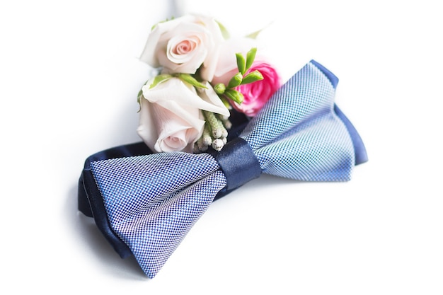 Le noeud papillon à carreaux bleu se trouve à côté de la boutonnière du marié isolé sur fond blanc
