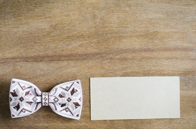 Noeud papillon et carte vide sur fond en bois.
