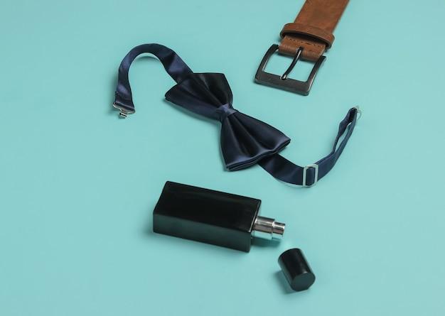 Noeud papillon, ceinture, flacon de parfum sur fond bleu. accessoires pour hommes, ensemble de style professionnel pour hommes. style formel, préparation du mariage.