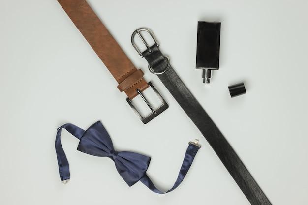 Noeud papillon, ceintures, bouteille de parfum sur fond blanc. accessoires pour hommes, ensemble de style professionnel pour hommes. style formel, préparation du mariage.