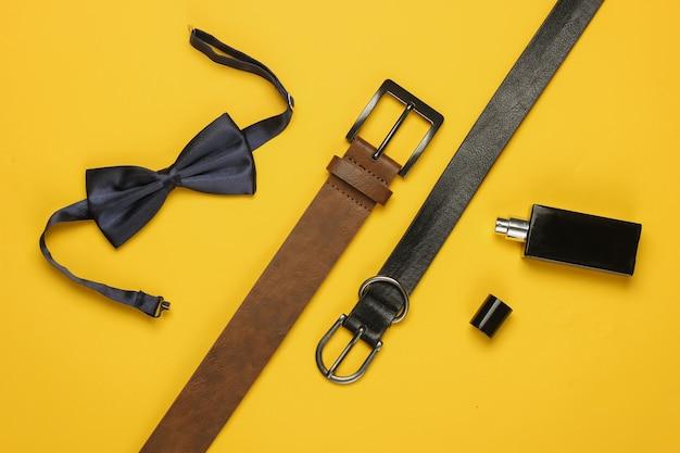 Noeud papillon, ceintures, bouteille de parfum sur fond jaune. accessoires pour hommes, ensemble de style professionnel pour hommes. style formel, préparation du mariage.