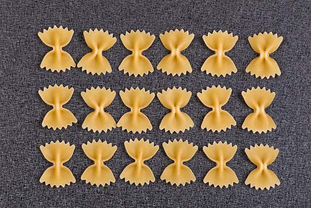Noeud papillon pâtes sur l'espace gris. farfalle non cuit. cuisine nationale italienne. espace culinaire.