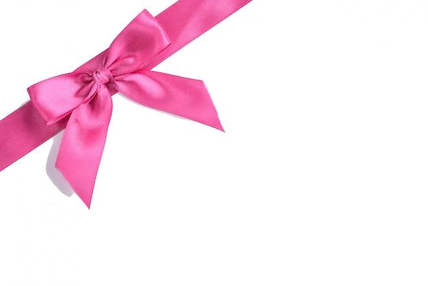 Noeud de ruban de satin rose isolé sur fond blanc.