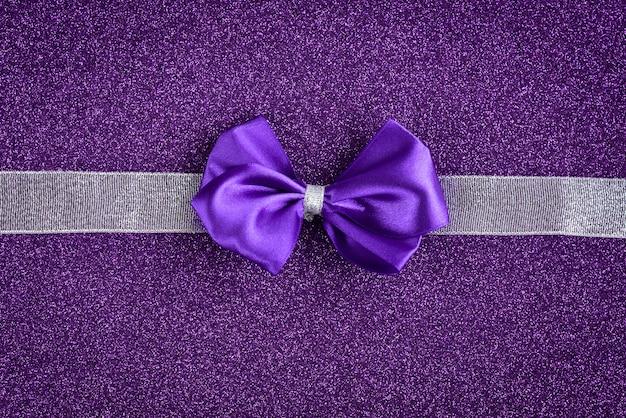 Noeud violet avec ruban argenté sur fond de paillettes violettes. contexte festif.