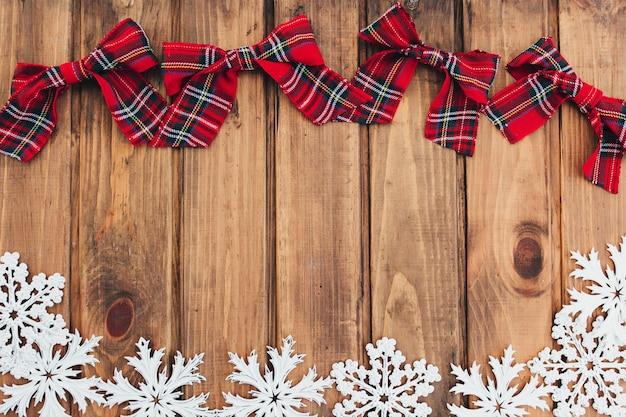 Noeuds rouges de noël et flocons de neige blancs sur bois brun.