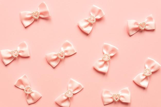 Noeuds en satin rose avec motif coeurs nacrés sur surface rose.
