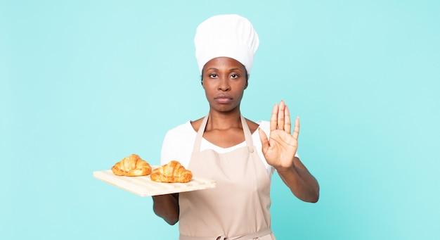 Noir afro-américain chef adulte femme tenant un plateau de croissants