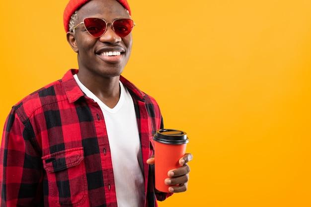 Noir américain élégant avec un beau sourire dans une chemise à carreaux rouge tient dans ses mains un verre de café jaune