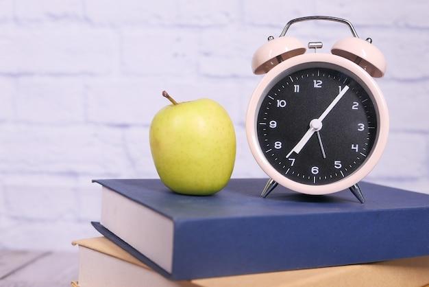 Noir au concept d'école avec apple et horloge sur les livres sur la table.