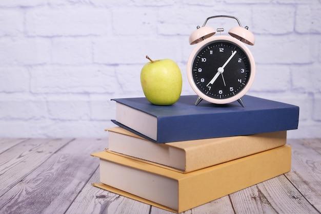 Noir au concept d'école avec apple et horloge sur pile de livres.