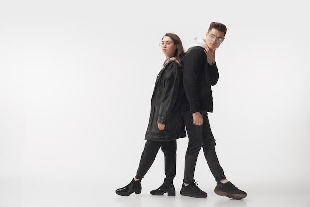 En noir. couple à la mode à la mode isolé sur le mur du studio blanc.