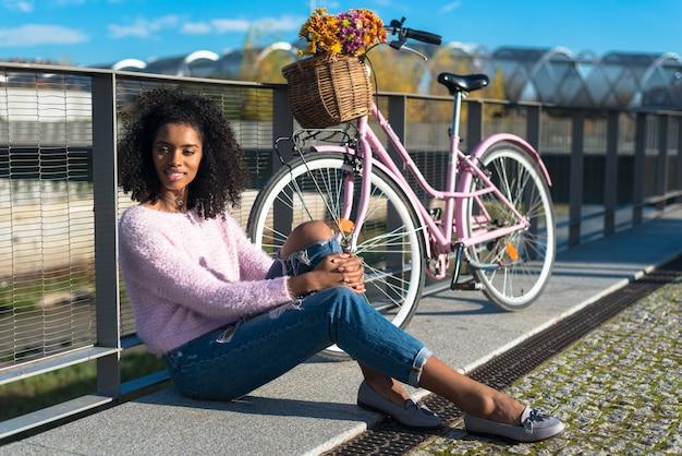 Noir jeune femme assise au bord de la rivière avec son vélo vintage