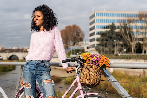 Noir jeune femme monté sur un vélo vintage