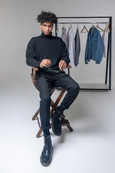 En noir. jeune homme afro-américain portant des vêtements noirs à la recherche de sérieux